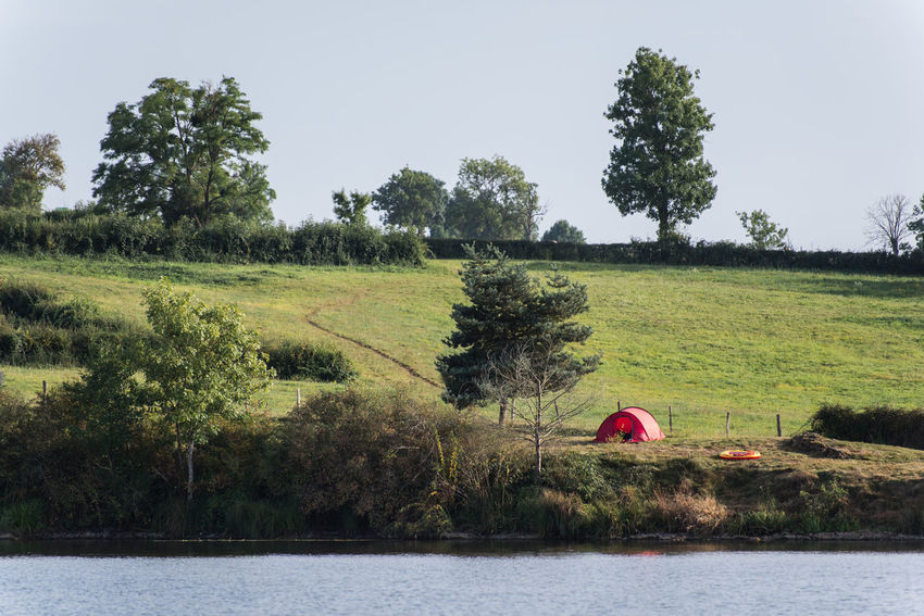 Lakeside Lake Buoy Tent Camping Plant Tree Sky Green Color Nature Water Landscape Growth Day Tranquility Beauty In Nature Tranquil Scene Land Field Grass Environment Scenics - Nature River Outdoors Calm Grassland Lakeshore Grass Area