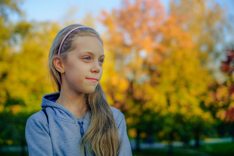 Girl standing at park during autumn