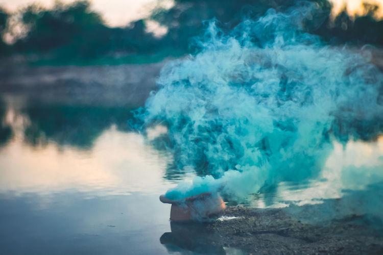 Flower pot emitting smoke by lake during sunset