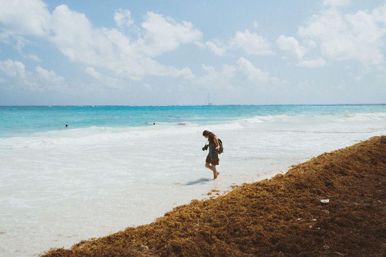 Full length of girl standing on beach against sky