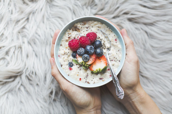 Bowl with porridge in hands on a fur background Berry Fruit Blueberry Bowl Breakfast Chia Seed Close-up Directly Above Food Food And Drink Freshness Fruit Granola Healthy Eating Healthy Lifestyle Holding Human Body Part Human Hand Indoors  Lifestyles One Person Raspberry Ready-to-eat Real People Smoothie Yogurt