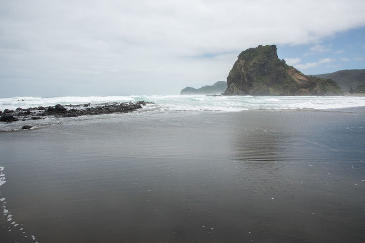 Piha Beach with volcanic black sand and Lion Rock in Auckland, New Zealand Auckland Lion Rock Spectacular Tasman Sea Beach Beauty In Nature Black Cloud - Sky Eroded Horizon Over Water Idyllic Land Landmark Nature New Zealand Piha Rock Rock - Object Sand Scenics - Nature Sea Tranquility Volcanic Landscape Volcano Water