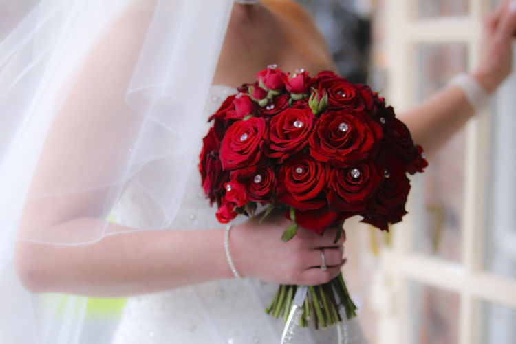 Midsection Of Bride Holding Red Roses