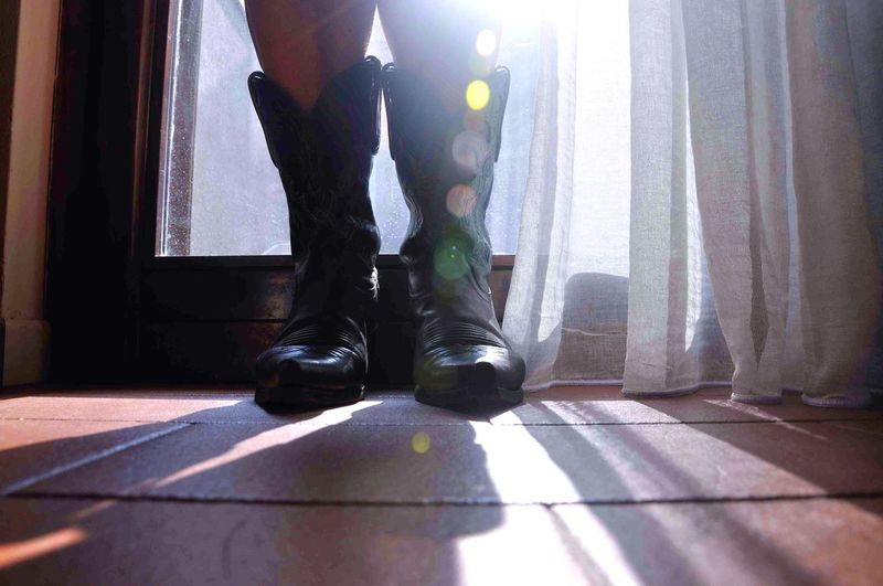Low section of person standing in cowboy boots by window at home