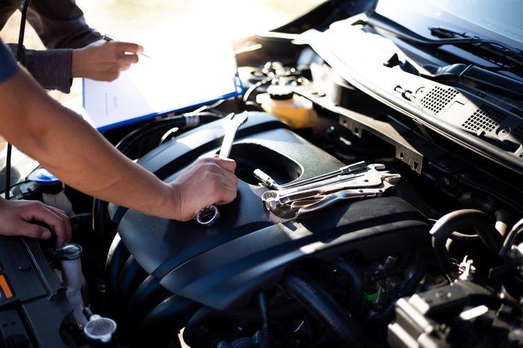 Cropped hand of mechanic repairing car engine in workshop