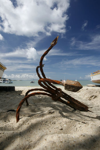 Rusty anchor at beach against sky