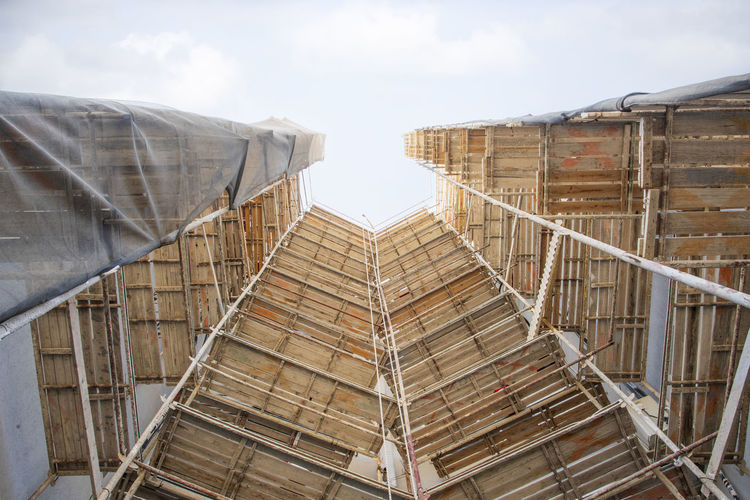Low angle view of building under construction against sky