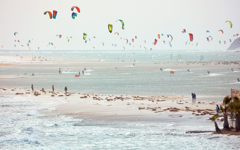 People parasailing over sea against sky