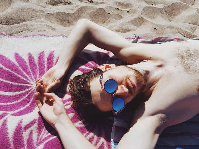 Directly Above Shot Of Young Man Lying On Sand At Beach