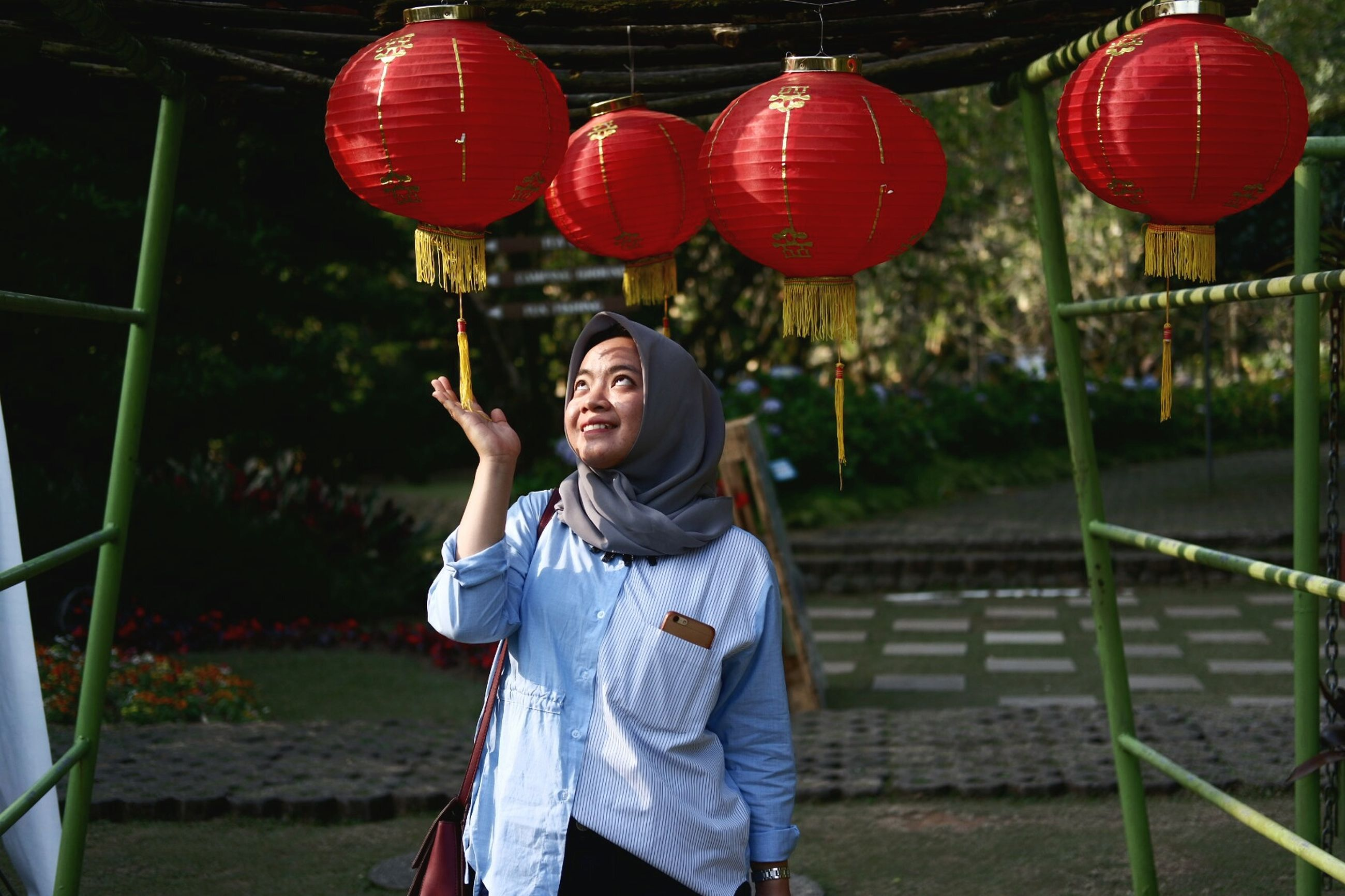 real people, one person, leisure activity, front view, standing, casual clothing, lifestyles, young adult, three quarter length, day, holding, happiness, women, red, smiling, nature, balloon, emotion, outdoors, chinese lantern