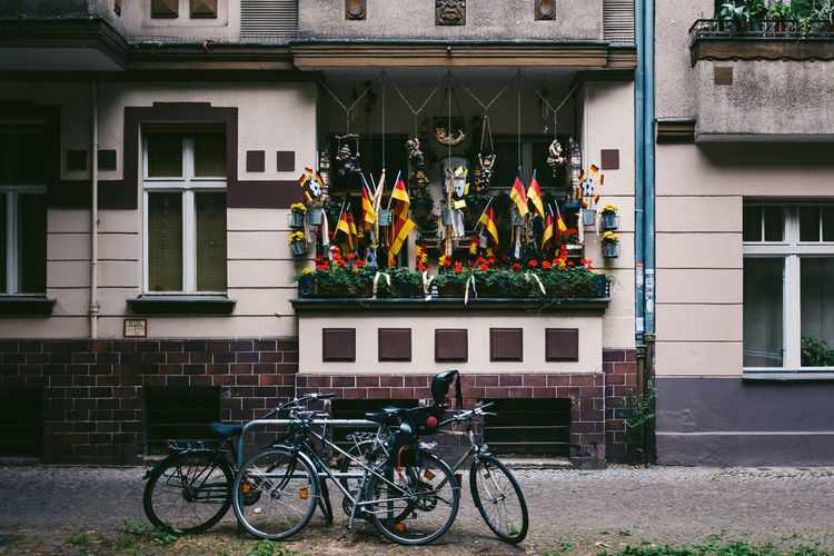 Bicycles Parked Outside Building With German Flags In Balcony
