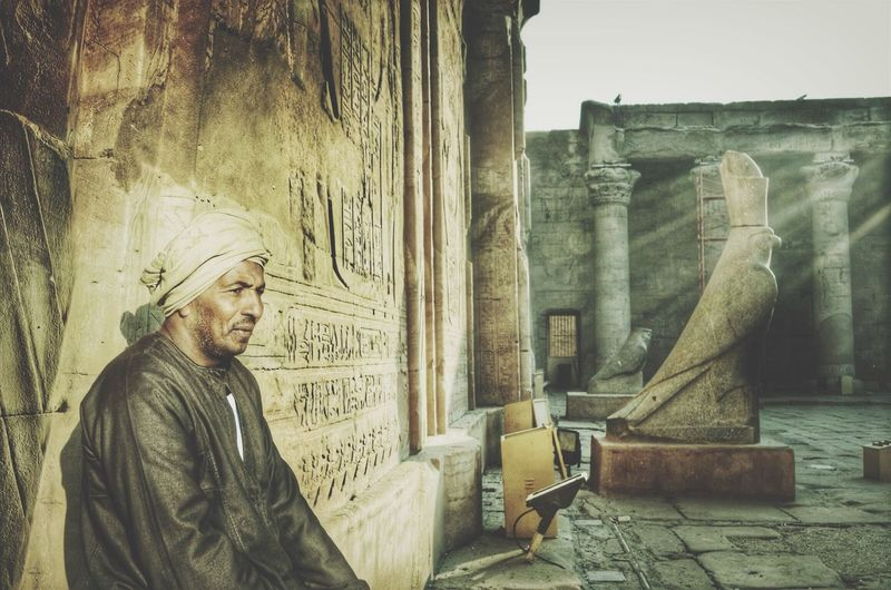 Thoughtful Mature Man Sitting By Temple Of Edfu