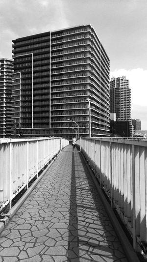 Person Walking On Footbridge Against Building
