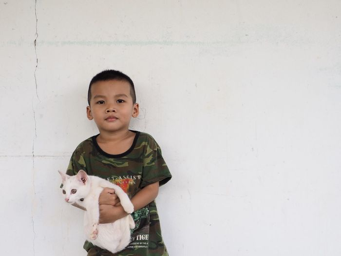 Portrait of cute boy with cat against white wall