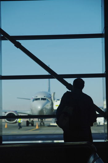 Air Vehicle Airplane Airport Airport Runway Clear Sky Day Journey Men Mode Of Transport One Person Outdoors People Public Transportation Real People Rear View Runway Silhouette Sky Standing Transportation Travel