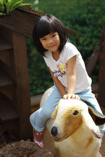 Portrait of cute smiling girl sitting on artificial sheep