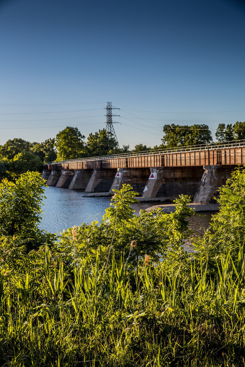 plant, sky, water, architecture, built structure, nature, dam, clear sky, tree, fuel and power generation, bridge, hydroelectric power, connection, river, bridge - man made structure, renewable energy, day, no people, copy space, outdoors, flowing water