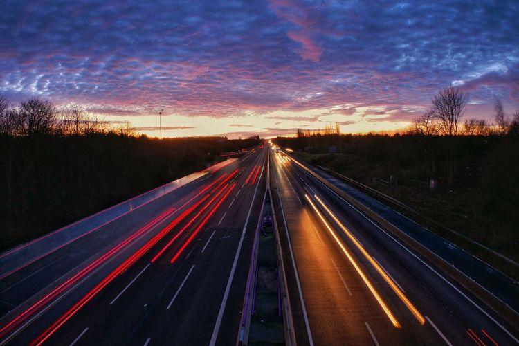 Light trails on highway at sunset