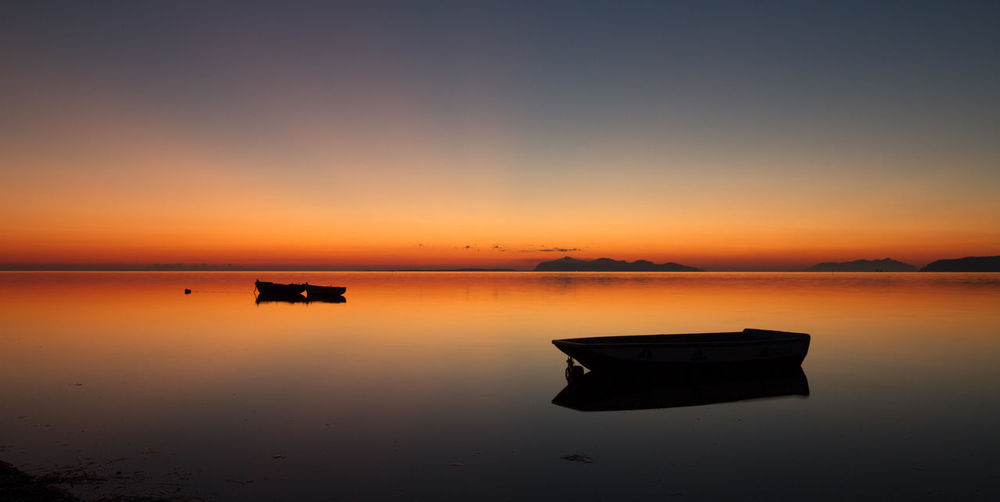 Silhouette of three boats at sunset, floating in a standing water