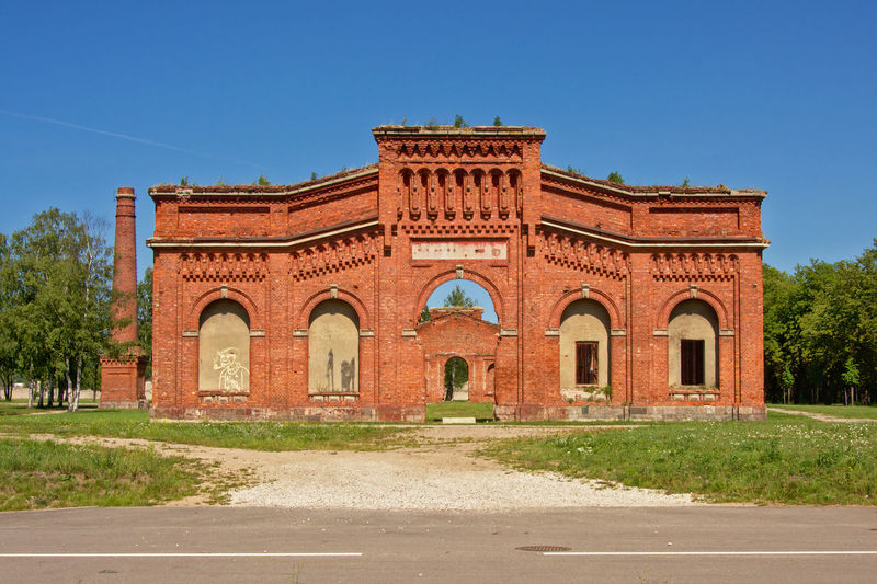 Front facade of the remains of the brick stone naval port manege building, part of the old military Soviet base near Lieapaja, Latvia Architecture Façade Latvia Liepaja Tourist Architecture Blu Sky Brick Building Building Exterior Built Structure Facade Building History Karosta Masonry Militay Aircraft No People Road Ruin Soviet The Past Tourism Travel Destinations Urbex Ussr