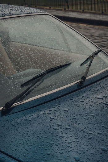 Raindrops over the windscreen and bonnet of a car on a rainy autumn day.