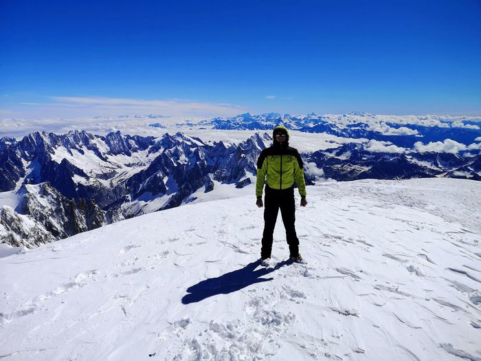 Full length rear view of man walking on snowcapped mountain