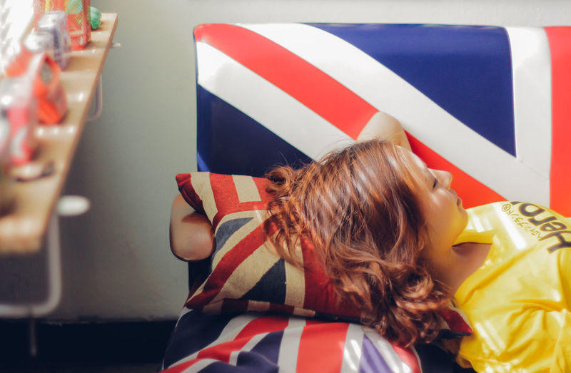 Flag Real People One Person Patriotism Striped Women Hair Indoors  Hairstyle Lifestyles Rear View Child Blond Hair Celebration Long Hair Shape Childhood Independence Relaxing Sleeping Couch Sleepy Nap Time Fashion Room Interior