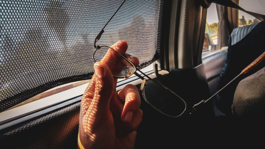 Cropped hand holding eyeglasses in car