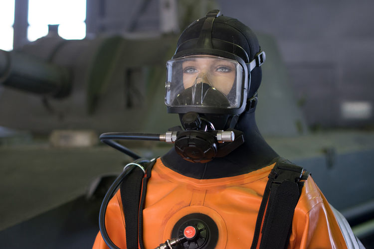 Woman In Protective Workwear Against Armored Tank