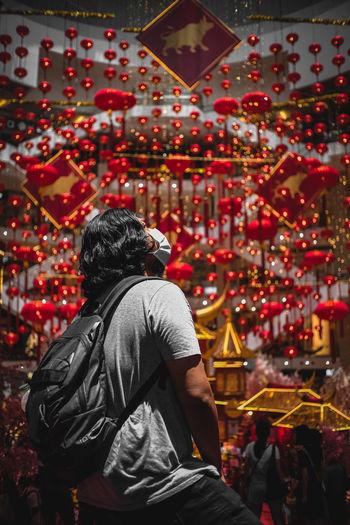 Rear view of man standing watching chinese lanterns
