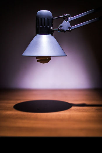 Close-up of electric lamp hanging on table