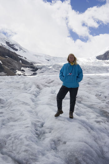 Full length of woman standing at columbia icefield against sky