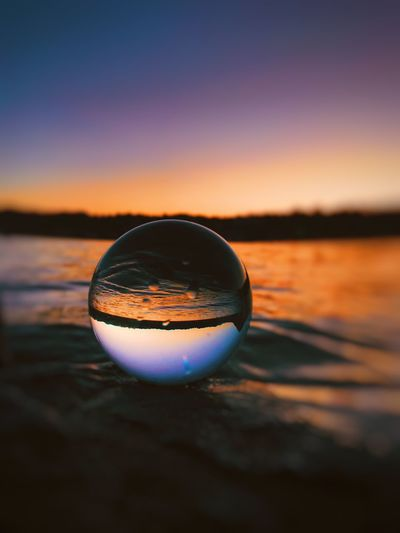 Close-up of crystal ball on water against sky during sunset Sunset Sky Sphere Scenics - Nature Beauty In Nature Crystal Ball Reflection Nature No People Water Close-up Orange Color Tranquil Scene Glass - Material Tranquility Transparent Idyllic Ball Outdoors