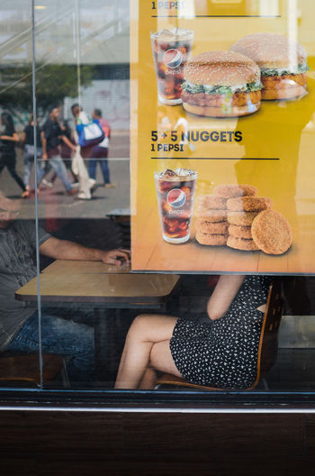 Nuggets The Art Of Street Photography Food And Drink Glass - Material Window Food Real People Store Sweet Food Text Transparent Retail  Incidental People Sweet Sitting Indoors  Casual Clothing Baked Reflection Day Business Retail Display Temptation EyeEm Best Shots EyeEm Selects Streetphotography Street Photography The Street Photographer - 2019 EyeEm Awards