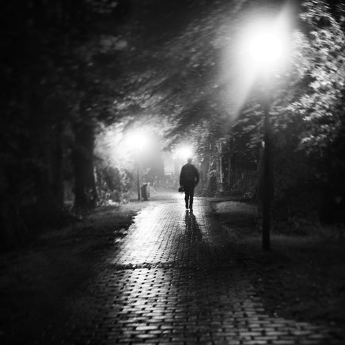 Woman walking on road at night