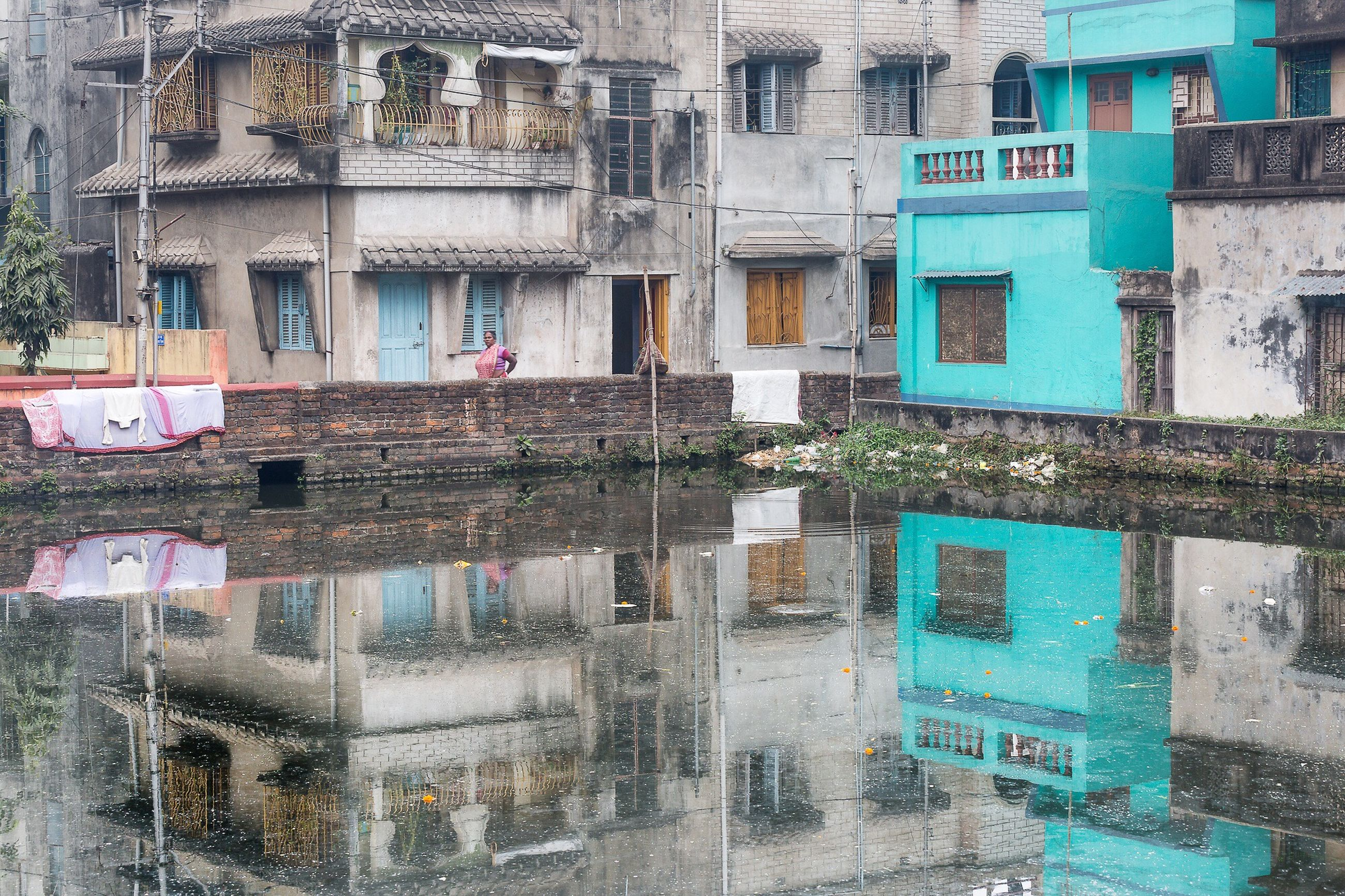 architecture, building exterior, built structure, building, residential building, water, residential structure, window, city, day, reflection, house, outdoors, no people, canal, transportation, old, damaged, multi colored, high angle view