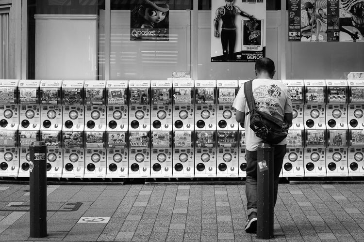 Capsules Real People Side By Side Full Length One Person Rear View Men Glass - Material Reflection Standing In A Row Arrangement Lifestyles Architecture Representation Leisure Activity Day Outdoors Container Human Representation Capsule Capsule Toys Japan Japan Photography Akihabara Monochrome Blackandwhite Black And White Black & White Streetphotography Street Urban City City Life City Street Relaxing Toys Canon Canonphotography The Traveler - 2019 EyeEm Awards The Street Photographer - 2019 EyeEm Awards Tokyo