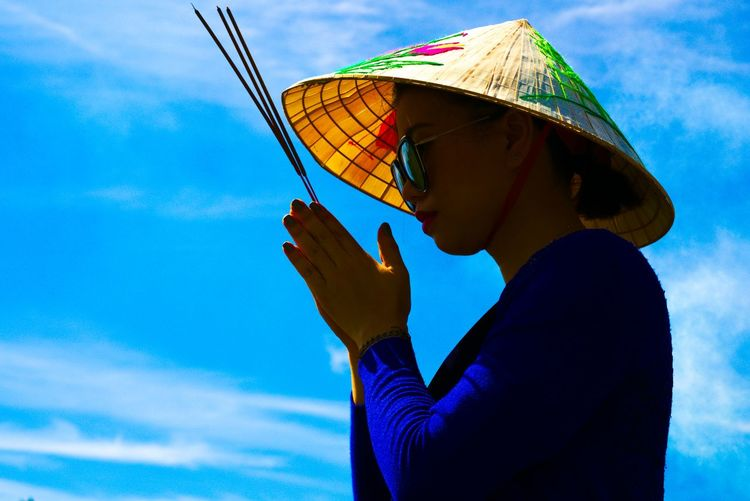 Woman Praying While Wearing Hat Against Blue Sky