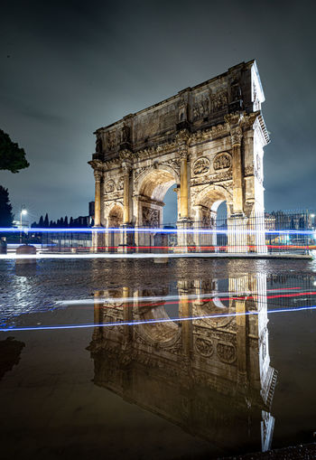 Long exposure night photo of constantine arch in rome, italy with light trails.