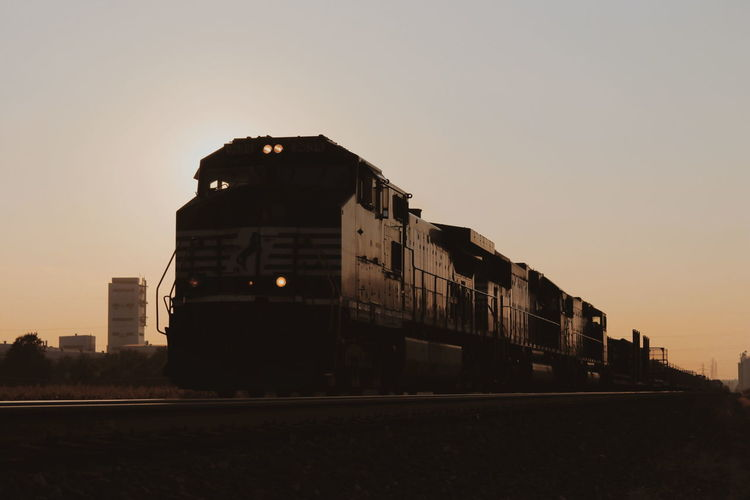 Train on railroad tracks against clear sky during sunset