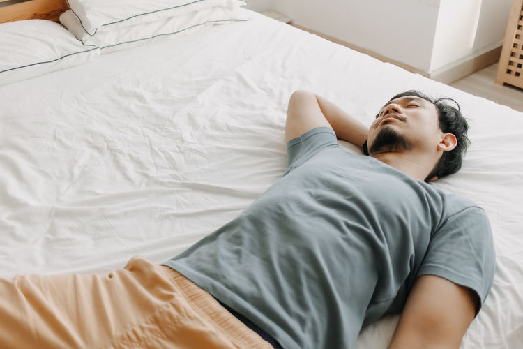 Young man sleeping on bed at home