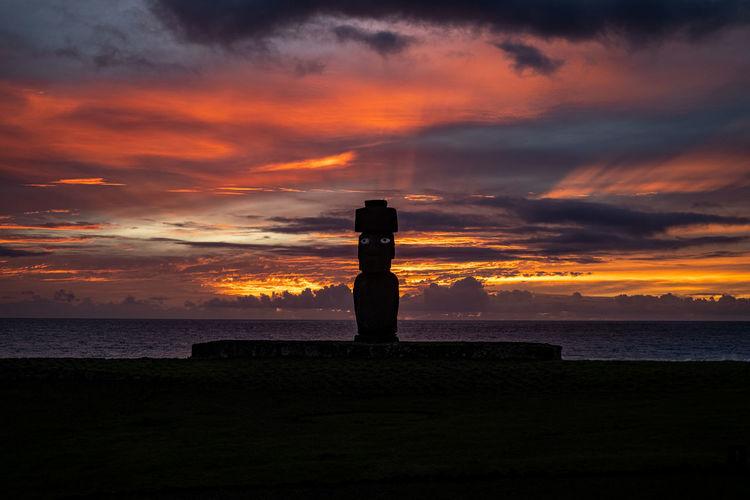 Silhouette cross on beach against sky during sunset