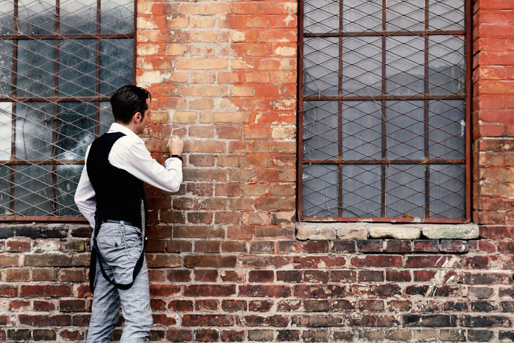 Side view of a man standing against brick wall