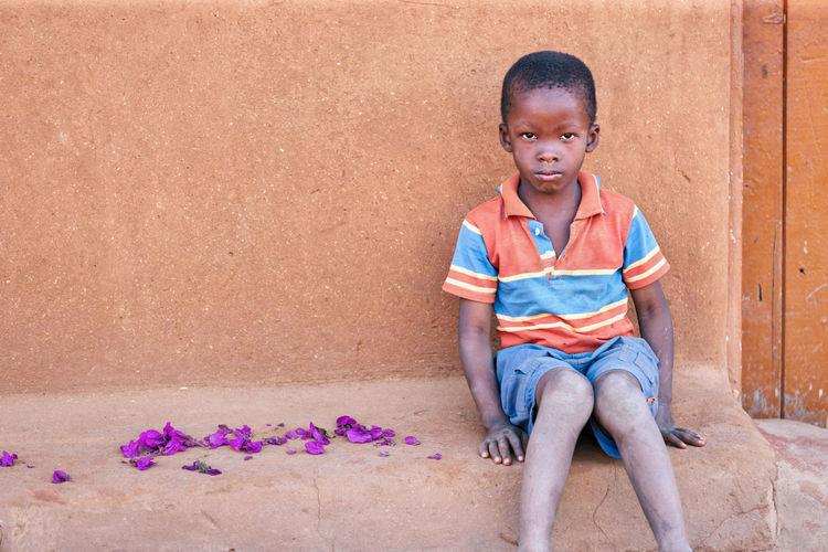 Portrait of boy sitting outdoors