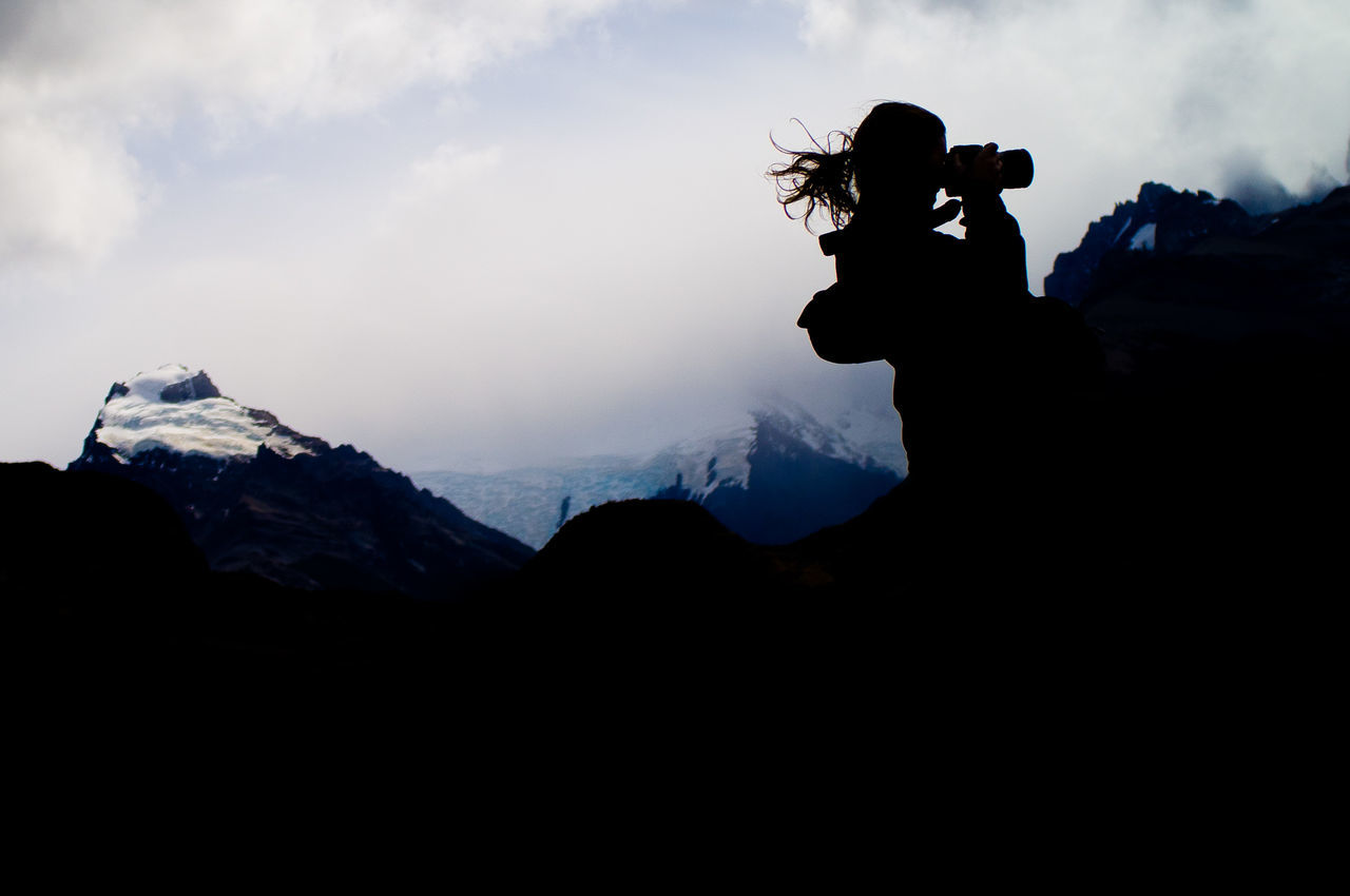 Young woman photographing in mountains