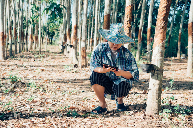 Full length of man sitting on field in forest