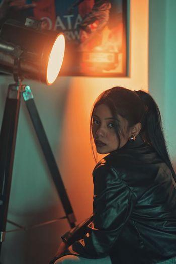 Portrait of woman standing against illuminated light