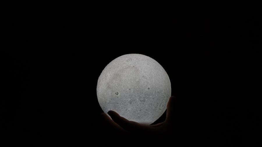 Close-up of hand holding moon over black background
