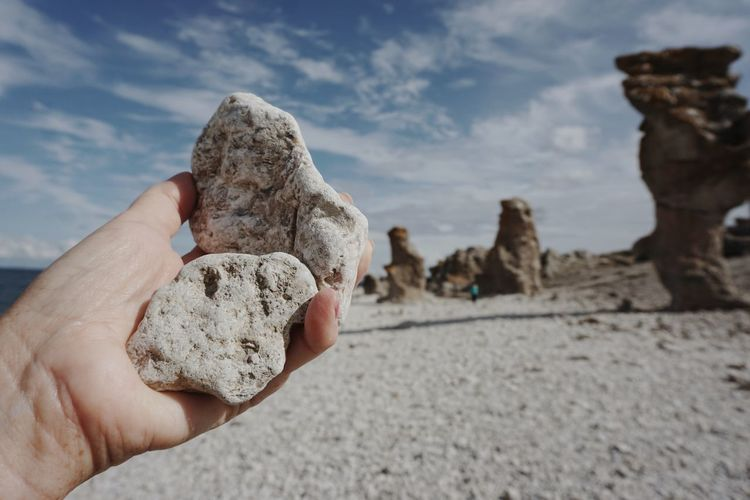 Close-Up Of Person Holding Rock Against Sky