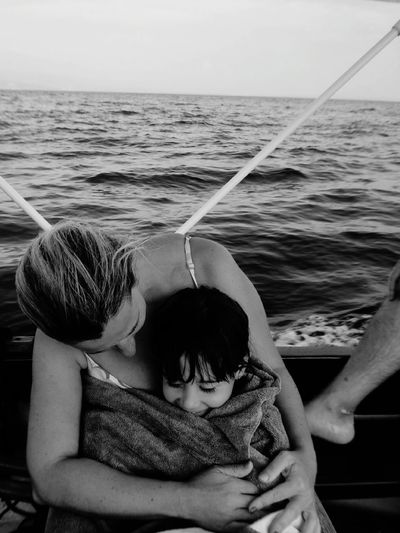 Woman With Daughter Sitting On Boat In Sea